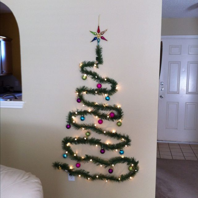 space-saving christmas tree made of pre-lit garland thumbtacked to