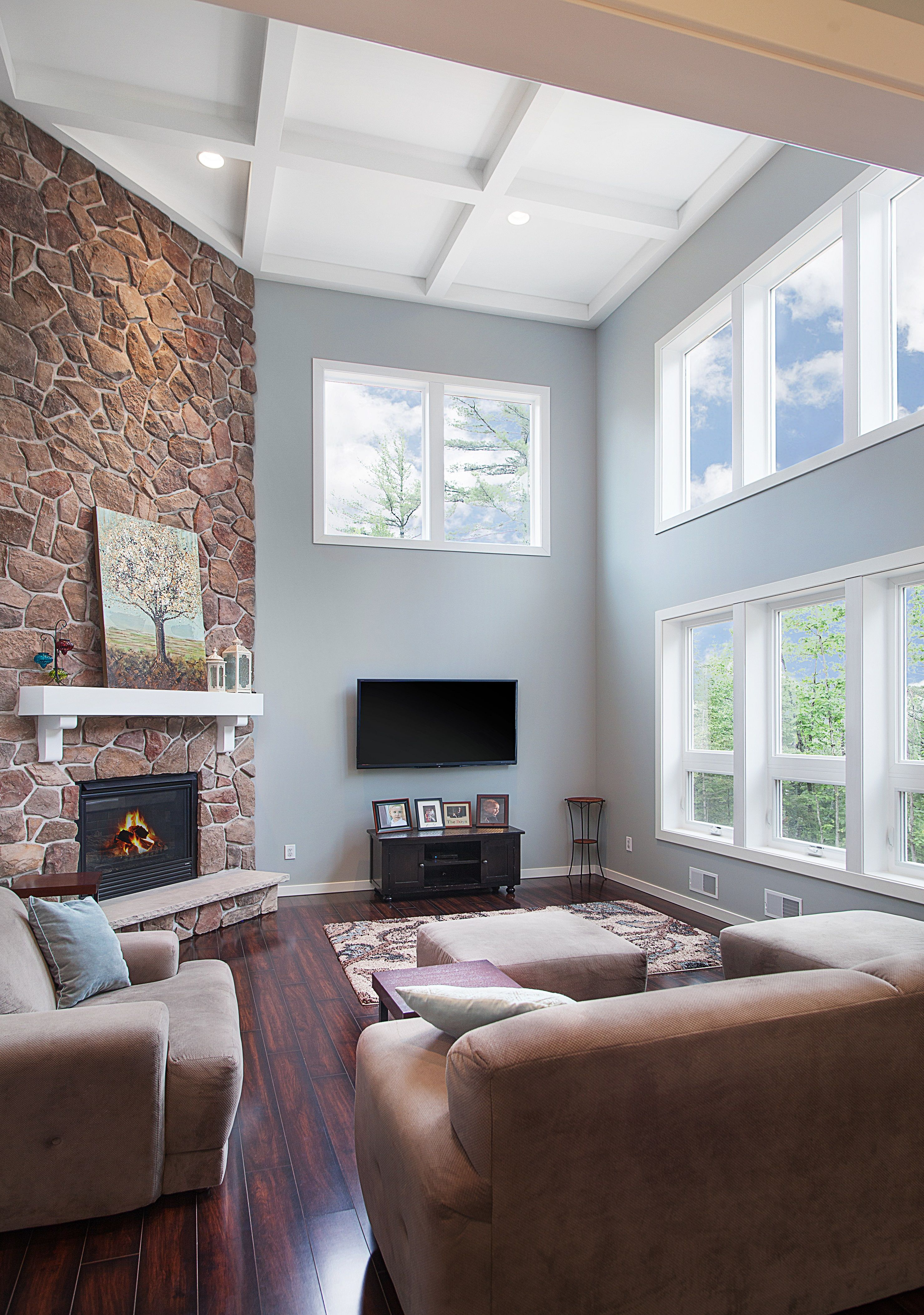 two story open great room with a coffered ceiling stone fireplace