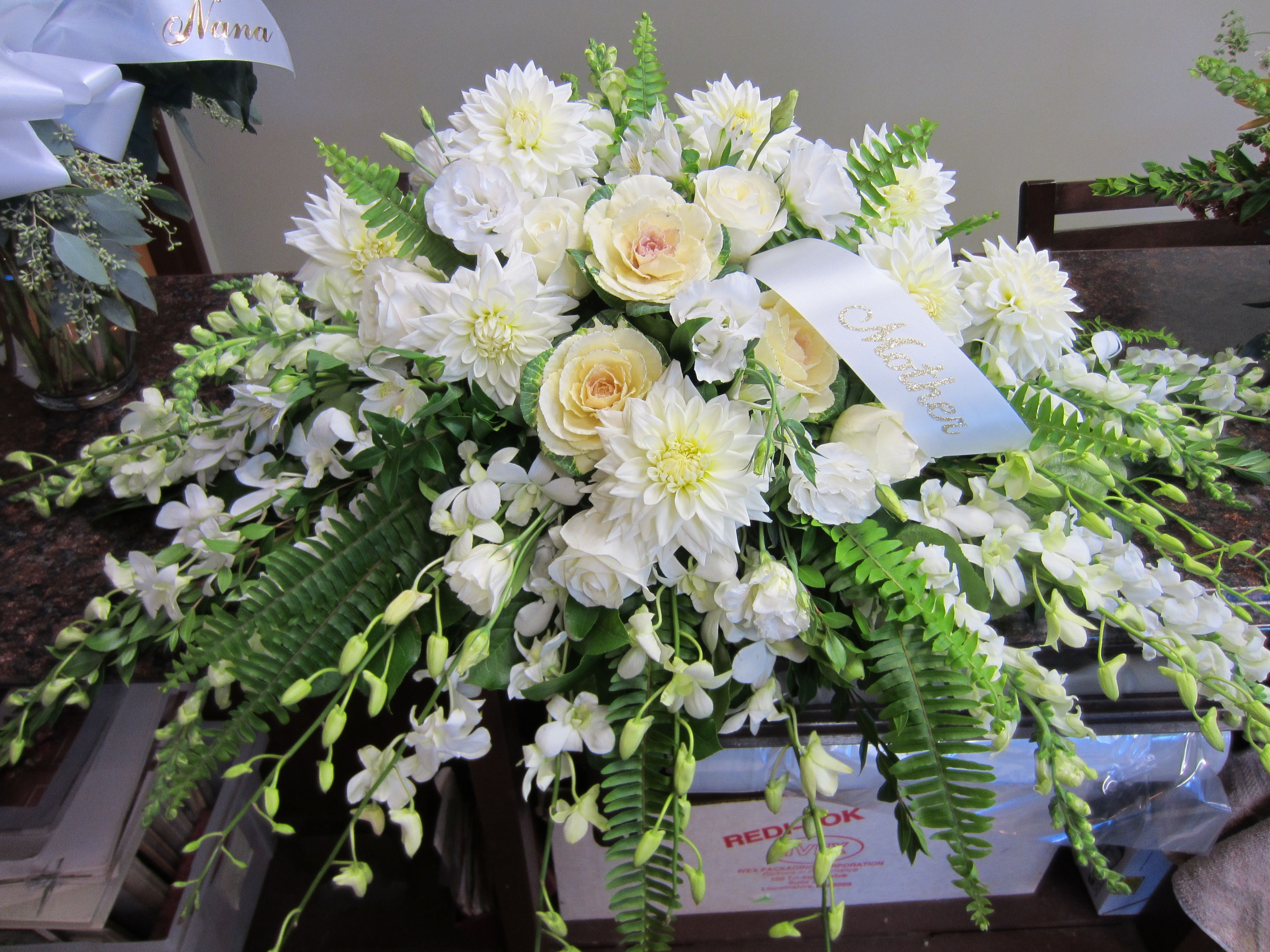 Shades Of White Flowers For The Casket Include Orchids Kale Dahlias And Roses Funeral Flowers Casket Flowers Funeral Flower Arrangements