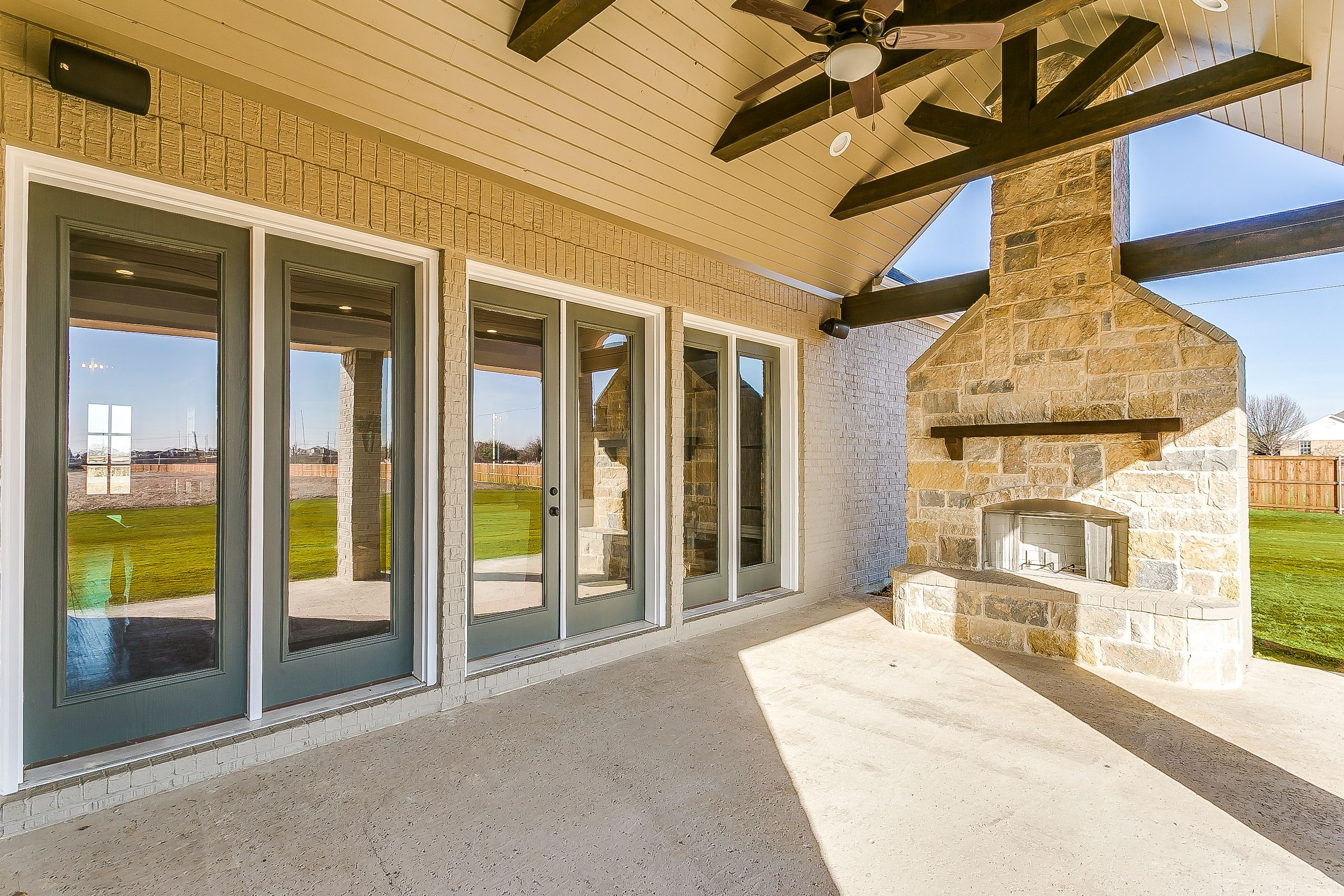 Covered patio with exposed beams rock fireplace legacy