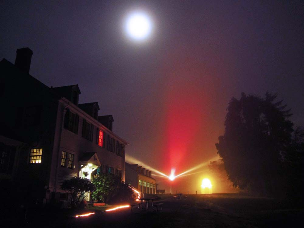 """""""Umpqua River Lighthouse on a Foggy Night"""" by Debbie Tegtmeier, 61, of Reedsport, was taken from the parkinglot of a museum in Winchester Bay. """"The beautiful carousel of red and white lights are always even more beautiful on a foggy night,"""" Tegtmeier says. """"Bonus of the Full Flower Moon being overhead."""" The photo made the 2013 Coast Weekend Top 25."""
