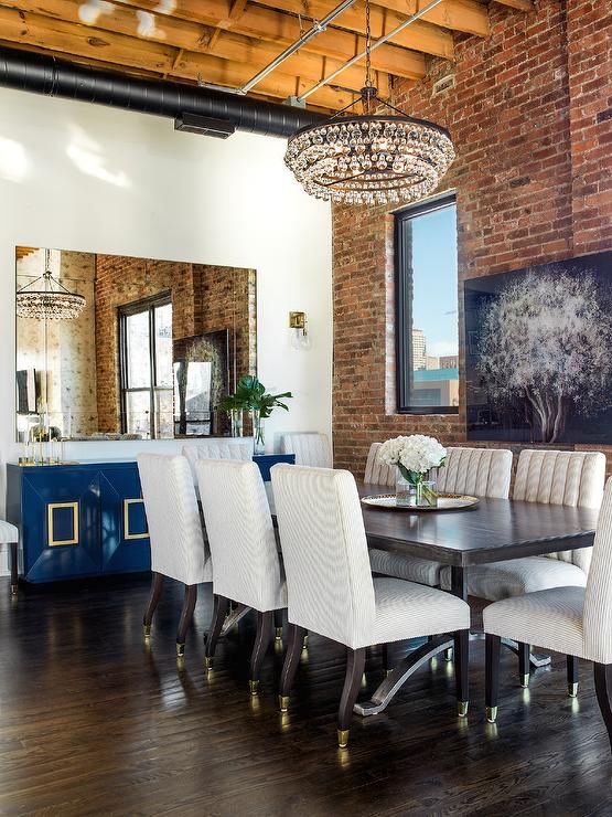 Loft Dining Room Features A Robert Abbey Bling Chandelier Illuminating A  Dark Dining Table Lined With Gray Striped Dining Chairs Atop A Stained Oak  Floor.