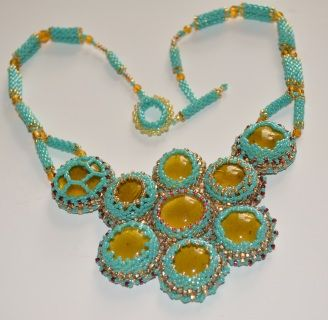 """Sunny yellow glass cabochons are framed by turquoise Japanese Seed Beads to form a lovely, distinctive cluster. Suspended from a rope of double peyote tubes, yellow fire-polished glass beads and finished with a hand-crafted clasp. Necklace is backed in soft turquoise and silver leather. Dimensions are 17"""" long, plus an additional 2 1/2"""" for the length of the cabochon cluster; measures 4"""" at the widest point."""