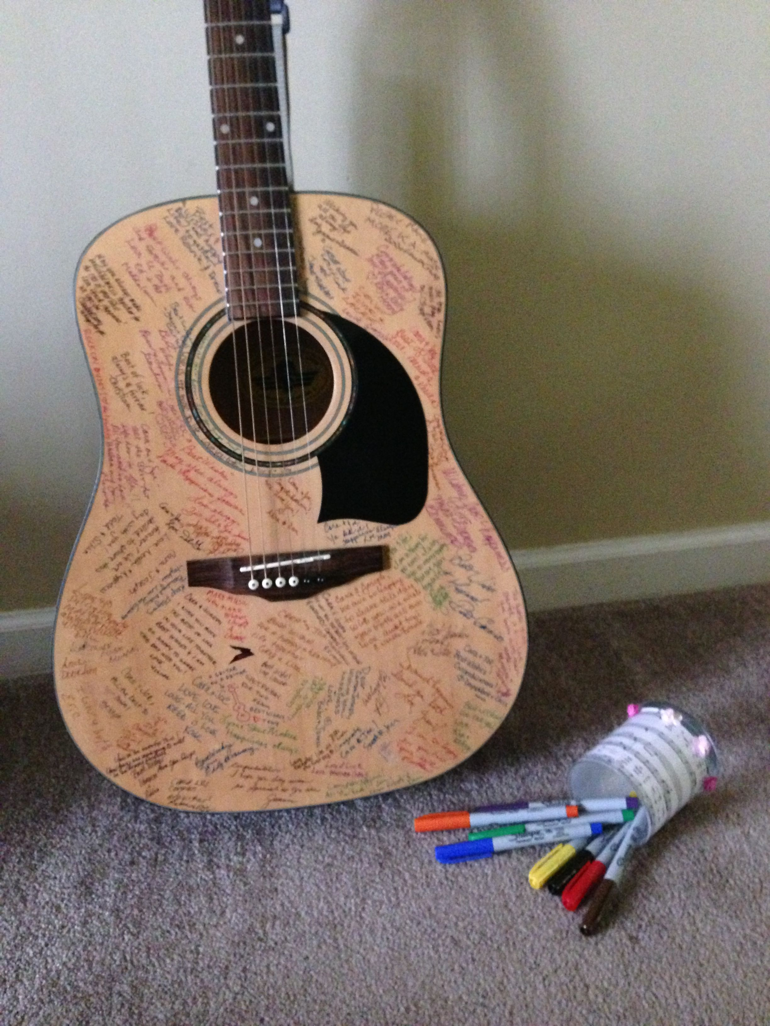 """Guitar Guest Book complete! Well-wishes from our Family and Friends were written using """"Sharpie Ultra Fine"""" Markers so they didn't smudge. We are going to hang this special piece of art on our wall in the near future so we will always remember how we first met. (Also, a reminder of how awesome our wedding day was!)"""