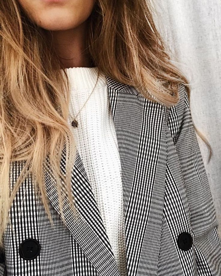 Simple white sweater with minimal jewelry and plaid blazer