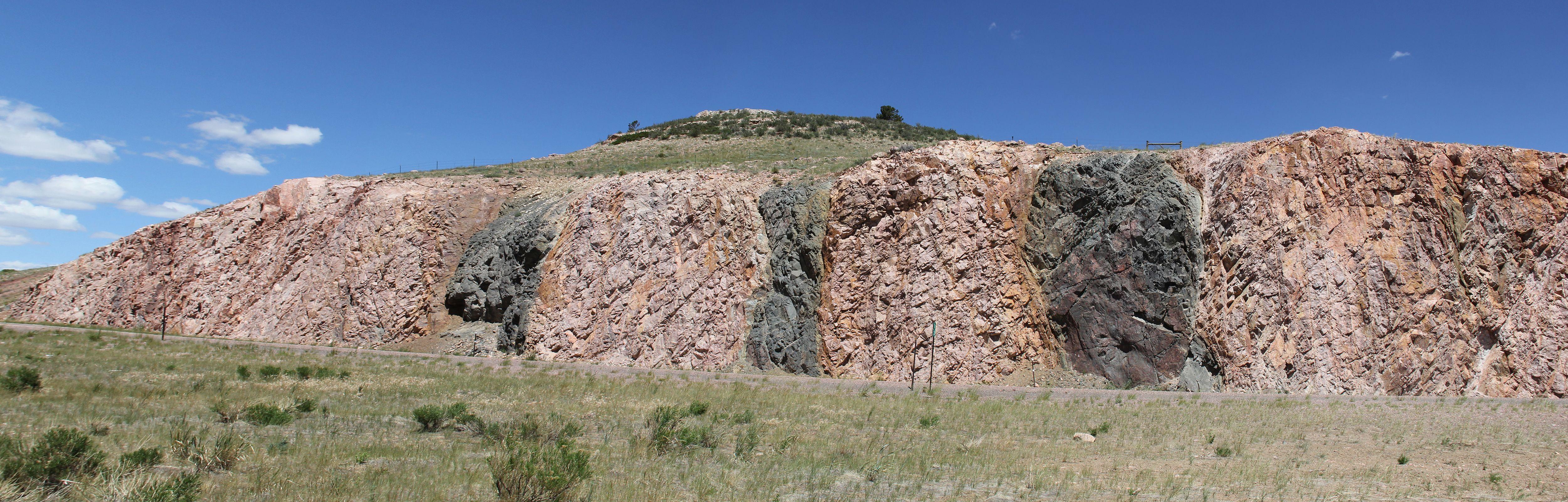 Laramie Range at Morton Pass, Wyoming.  Paleoproterozoic (ca. 2 bya) mafic dikes (dark) cross-cut an older Archean (ca. 2.7+ bya) granitic/gneissic complex (light). ...