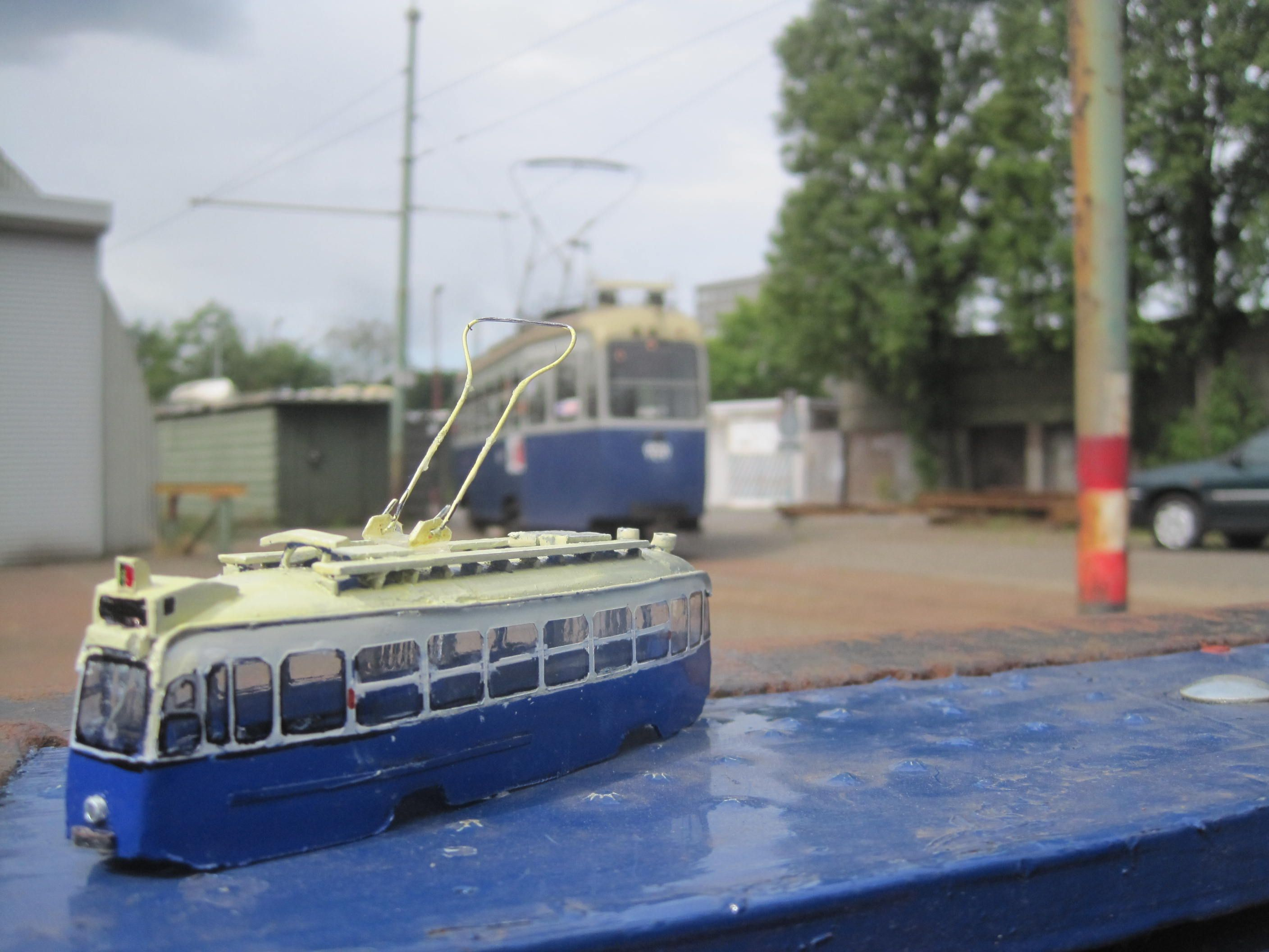 Model of a 3-axle tram,in the back the real thing