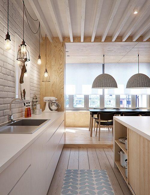 Cocina camuflada con pared de ladrillo blanco y mueble bajo