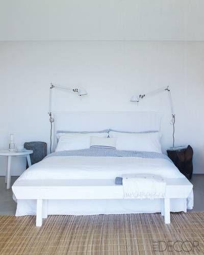 In a bedroom, a modern Gervasoni bed is framed  by Tolomeo lamps.   - ELLEDecor.com