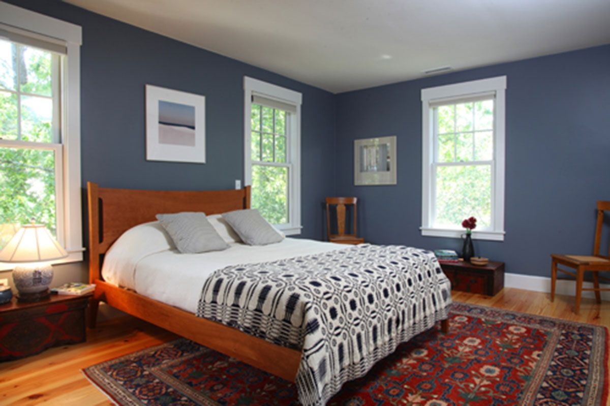Cape Cod bedroom featuring dark blue walls, matching bed set and ...