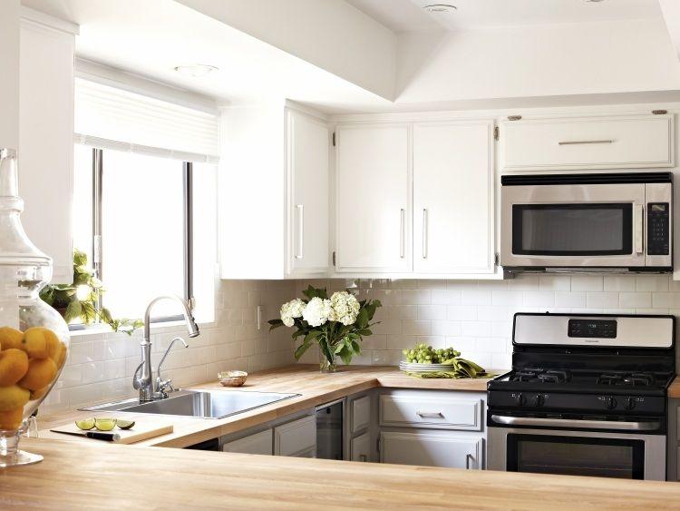 kleine Küche in U-Form mit weißem Fliesenspiegel und Holz ...