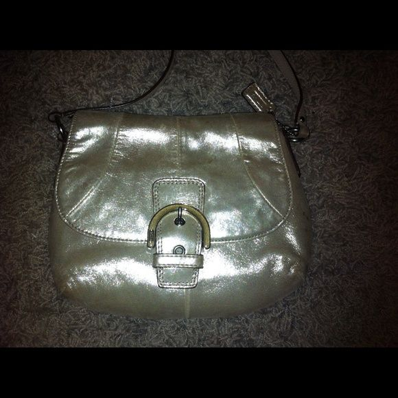 Authentic Coach Crossbody Purse- metallic leather Authentic Coach Crossbody purse/ beautiful shiny metallic like leather - goldish in color/ front is in good condition/ inside has a stain (see pic) and back side shows wear from rubbing against clothes and some spots/ still really pretty bag- but be aware of imperfections before purchase :) Coach Bags Crossbody Bags