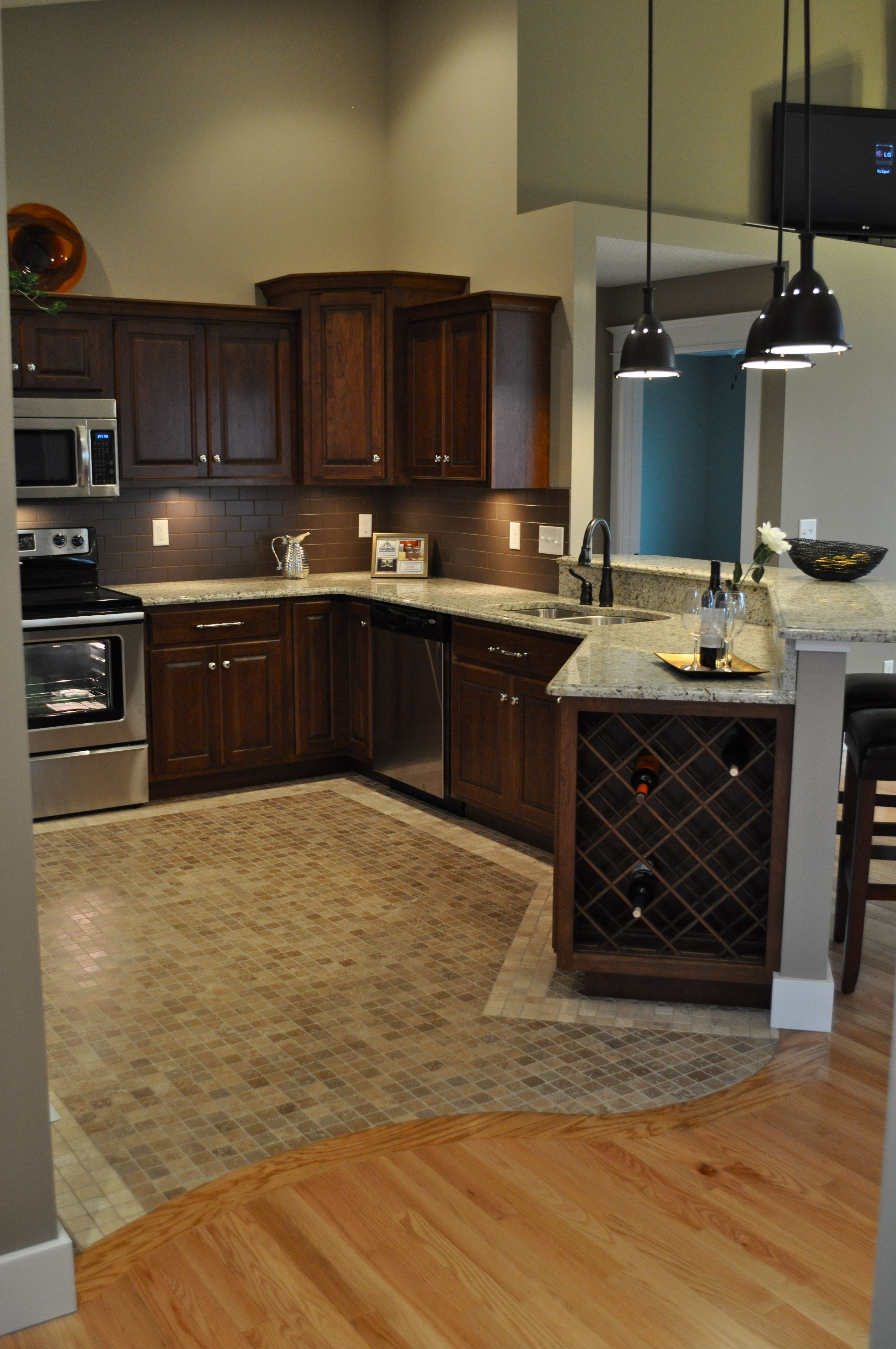 Oak hardwood floors with curved transition to mosaic travertine tile