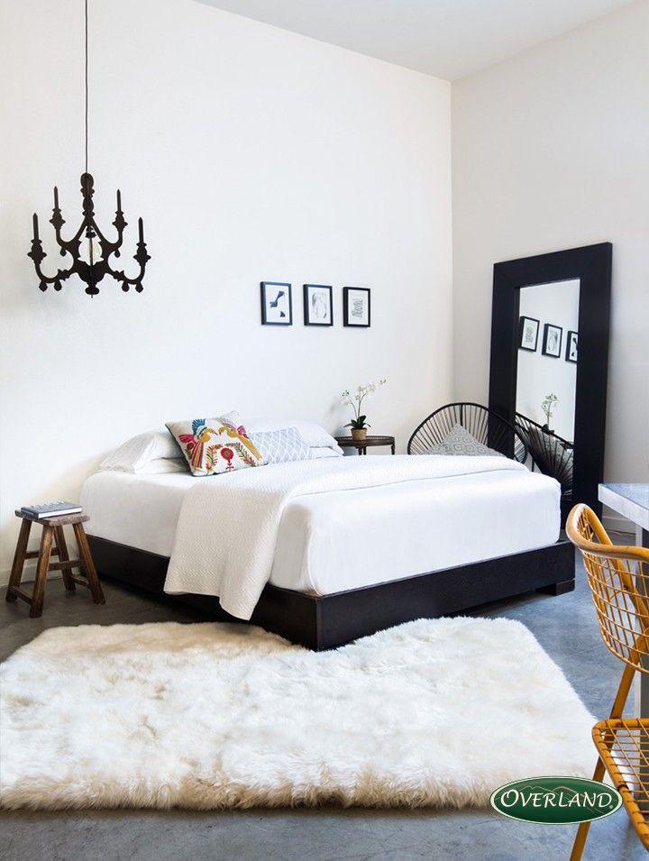 Chambre adulte, épuré. Grand tapis blanc sur un sol en béton ciré. Grand miroir noir.