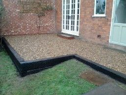Railway sleeper walls and gravel patio built in rear ...