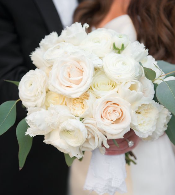a textured ivory bouquet with blush and green accents incorporating garden roses ohara roses fringed tulips ranunculus and flat eucalyptus