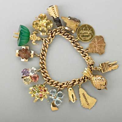 """18K GOLD CHARM BRACELET WITH CHARMS, ca. 1960; Curb link bracelet suspends fourteen charms including native woman naughty, 6 1/2""""; ballerina with chrysoprase skirt; jeweled bouquet; fairy stone; etc.; 
