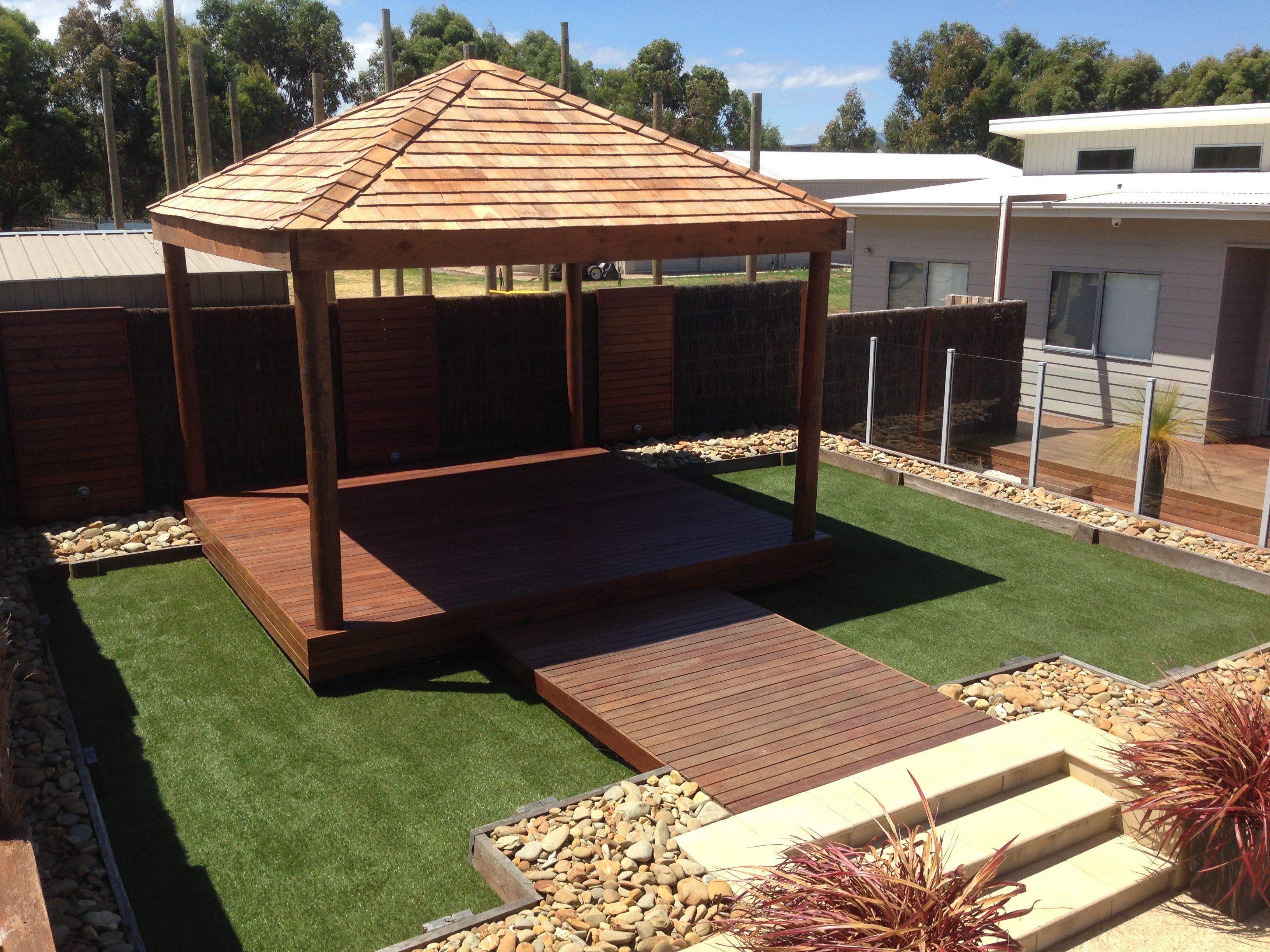 Tarima exterior cesped artificial pergola y un borde o for Small garden huts