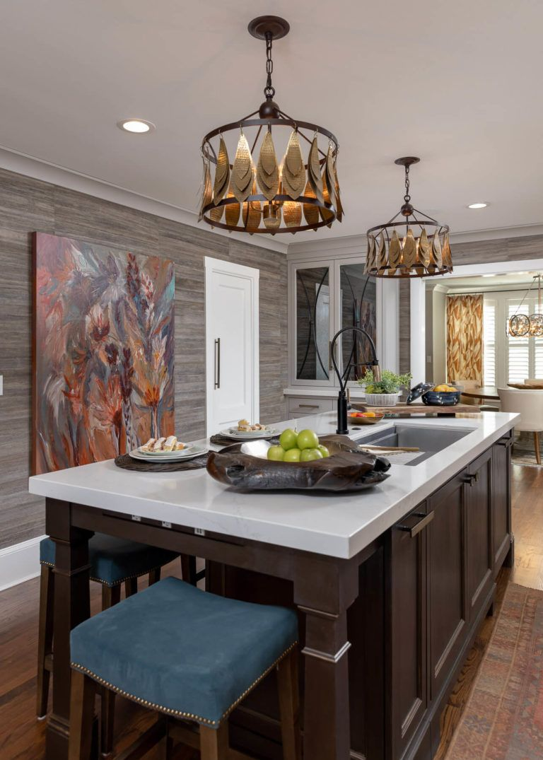 This beautiful kitchen features statement lighting, dark wood details, and striking artwork to tie the room together. Click to see more!  #kitchendetails #kitchendesign #indetailinteriors #traditionalstyle #coastalstyle #coastalliving #kitchenrenovation #kitchenmakeover #homebeforeandafter #homerenovation #homedesign