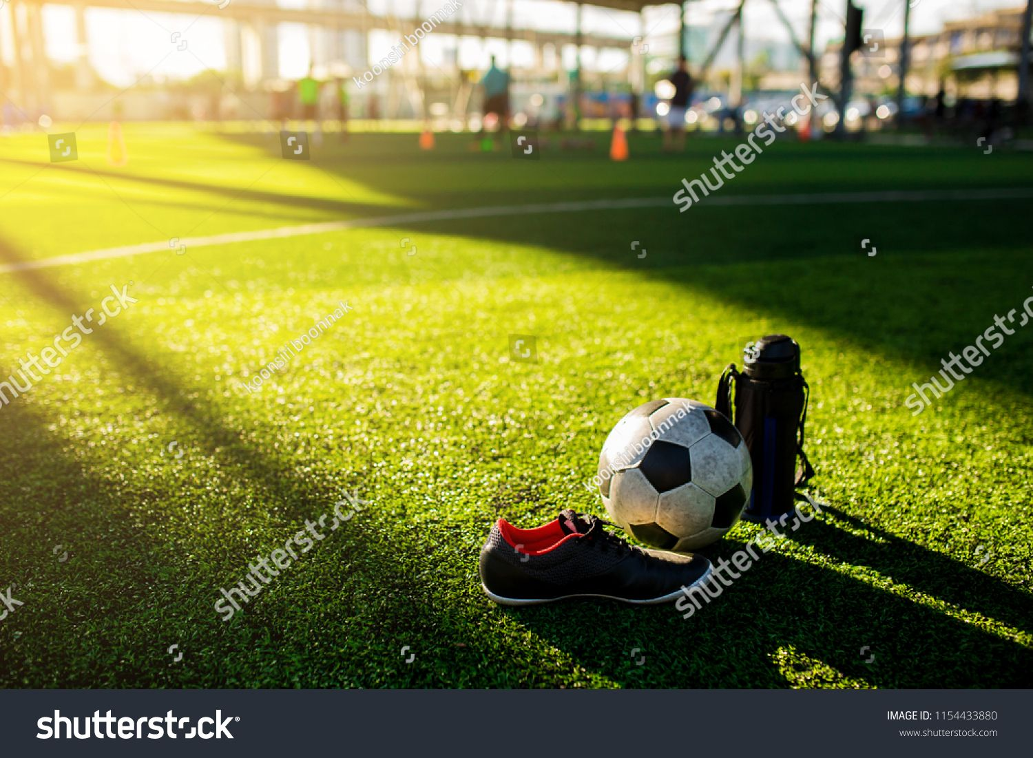 Football Cool Flask And Black Red Sports Shoes On Green Artificial Turf With Blurry Kid Soccer Player Red Sport Shoes Soccer Training Equipment Black And Red