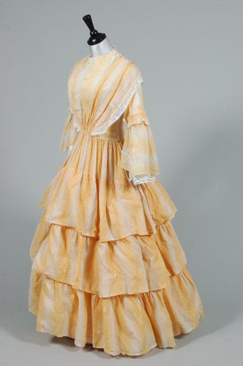 Two printed cotton 1850s day dresses, the first of pink and white trellis-weave muslin printed with fruits, fan-pleated front bodice with peplum to the waist; the other of mustard and white roller printed cotton with pagoda sleeves, tiered skirt, later added broderie anglaise cuffs and collar , 320 £