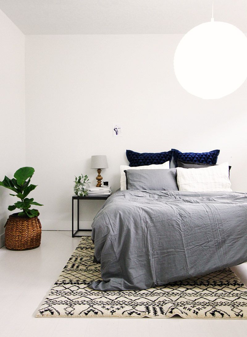 shades of gray in the bedroom with big white light fixture and indoor plant