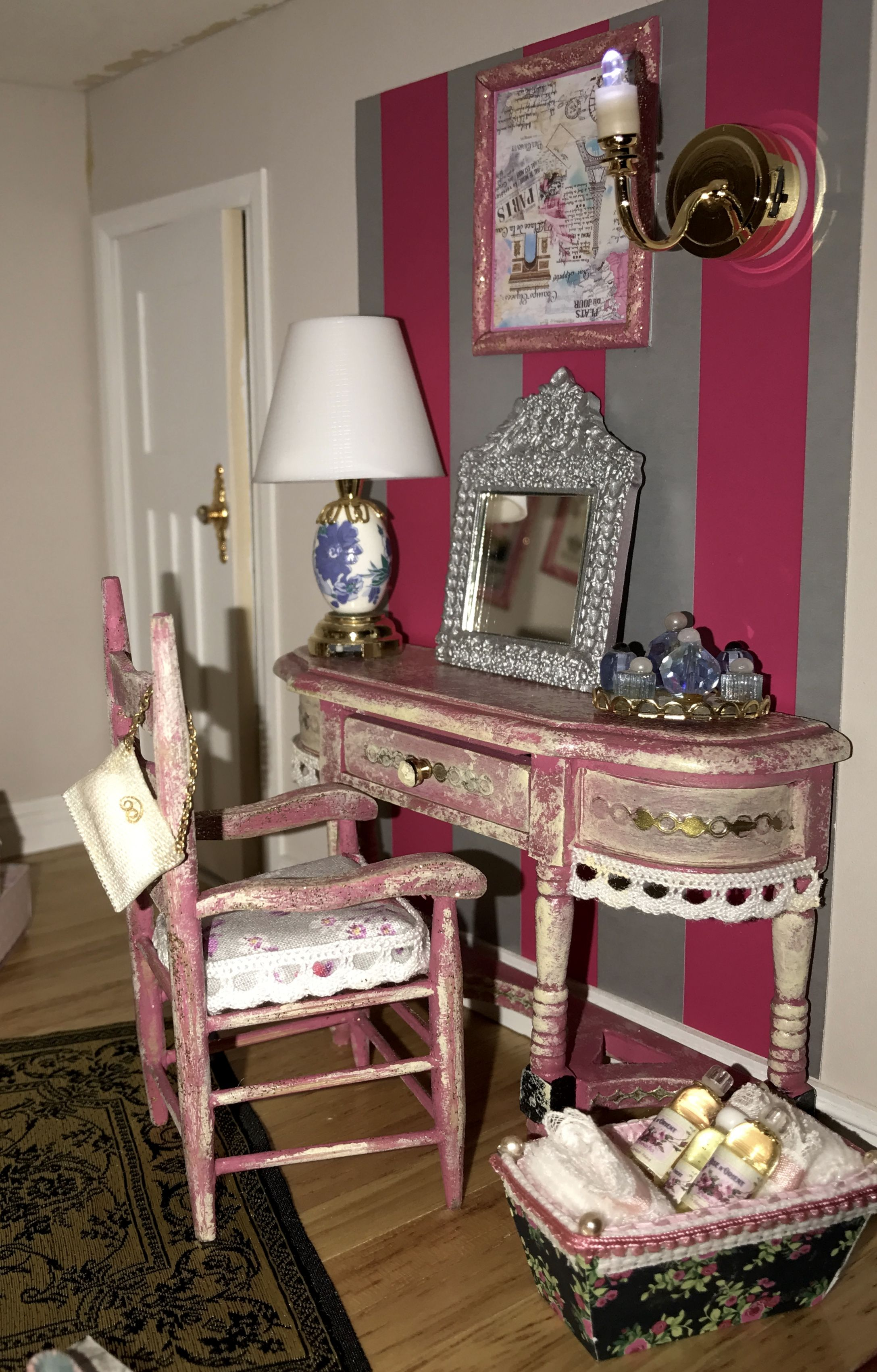 The right side of the bedroom shows a beautiful dressing table. The furniture has been bought naked and painted by Dany's DIY Minis, as well as the basket you see on the botton right of this pictures, and the soap bottles inside. Also the painting is a DIY item  by Dany's DIY Minis