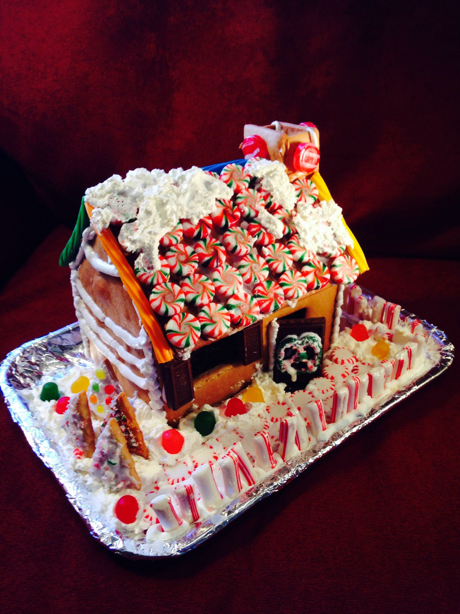 Gingerbread house with a light snow fall on the red white
