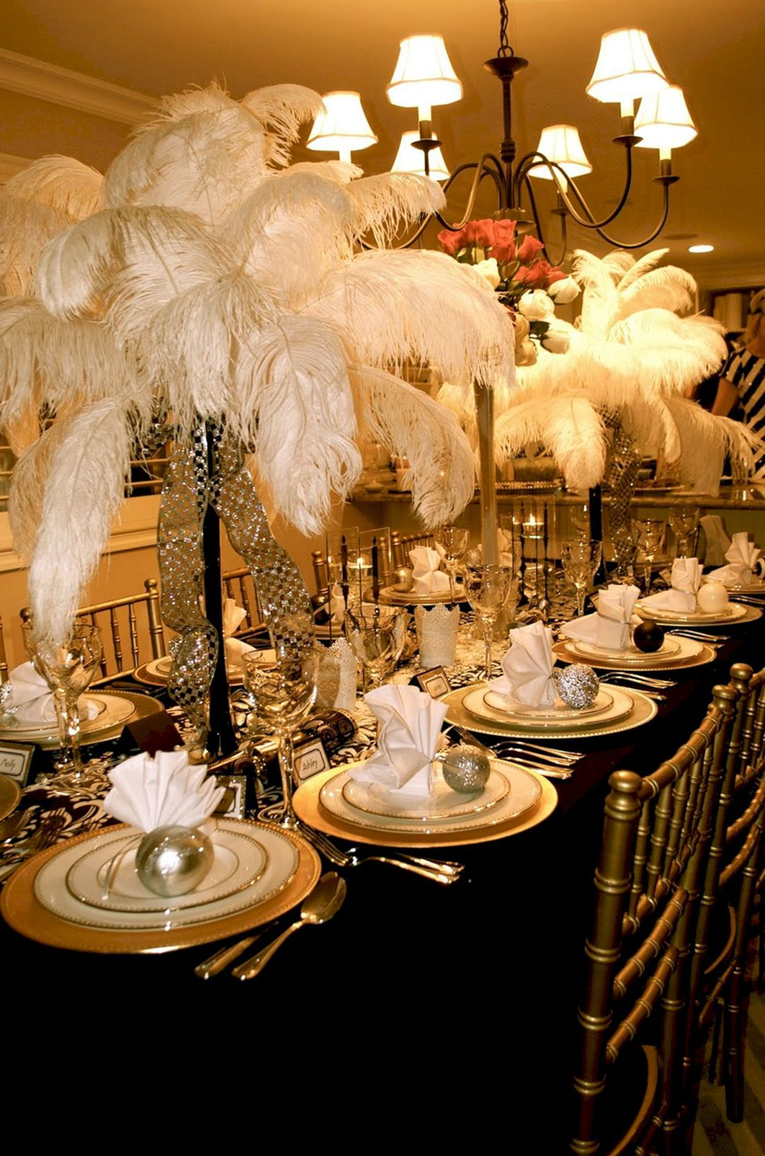 Great Gatsby party decorations - The feathers obviously look great, but I'm  pinning because of the way the napkins are folded and tied to an ornament  ...