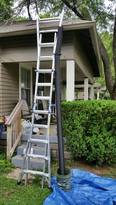 Cleaning gutters like a boss. All you need is a ladder, drain tile, garden spade and a bucket