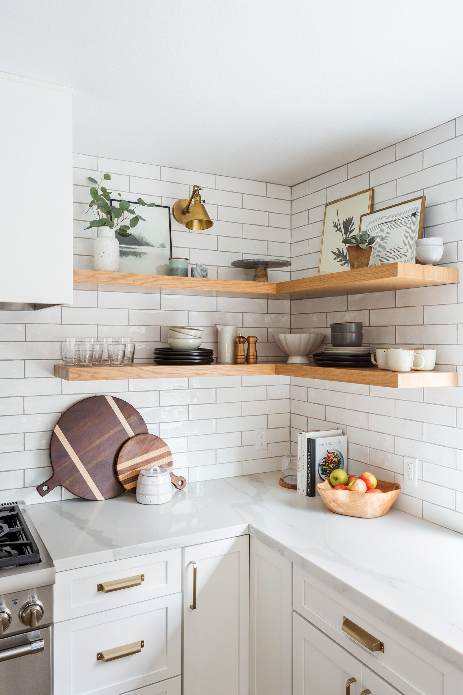 Photo of Oak Hills Kitchen Remodel: Modern white kitchen with subway tiles + statement lighting by Lindsey Bro…