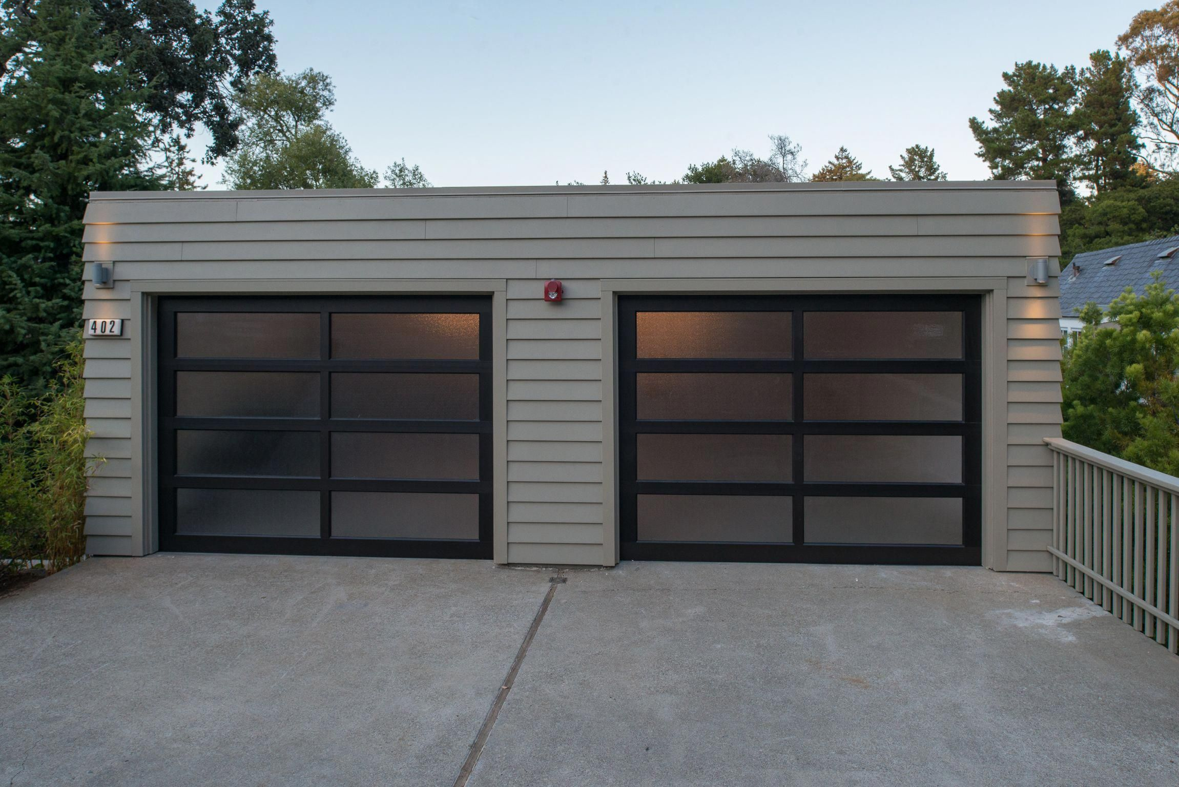 A Contemporary Garage With Beige Siding And A Black Framed Garage Door The Flat Top Roof And Unique Garage Doors Contemporary Garage Doors Modern Garage Doors