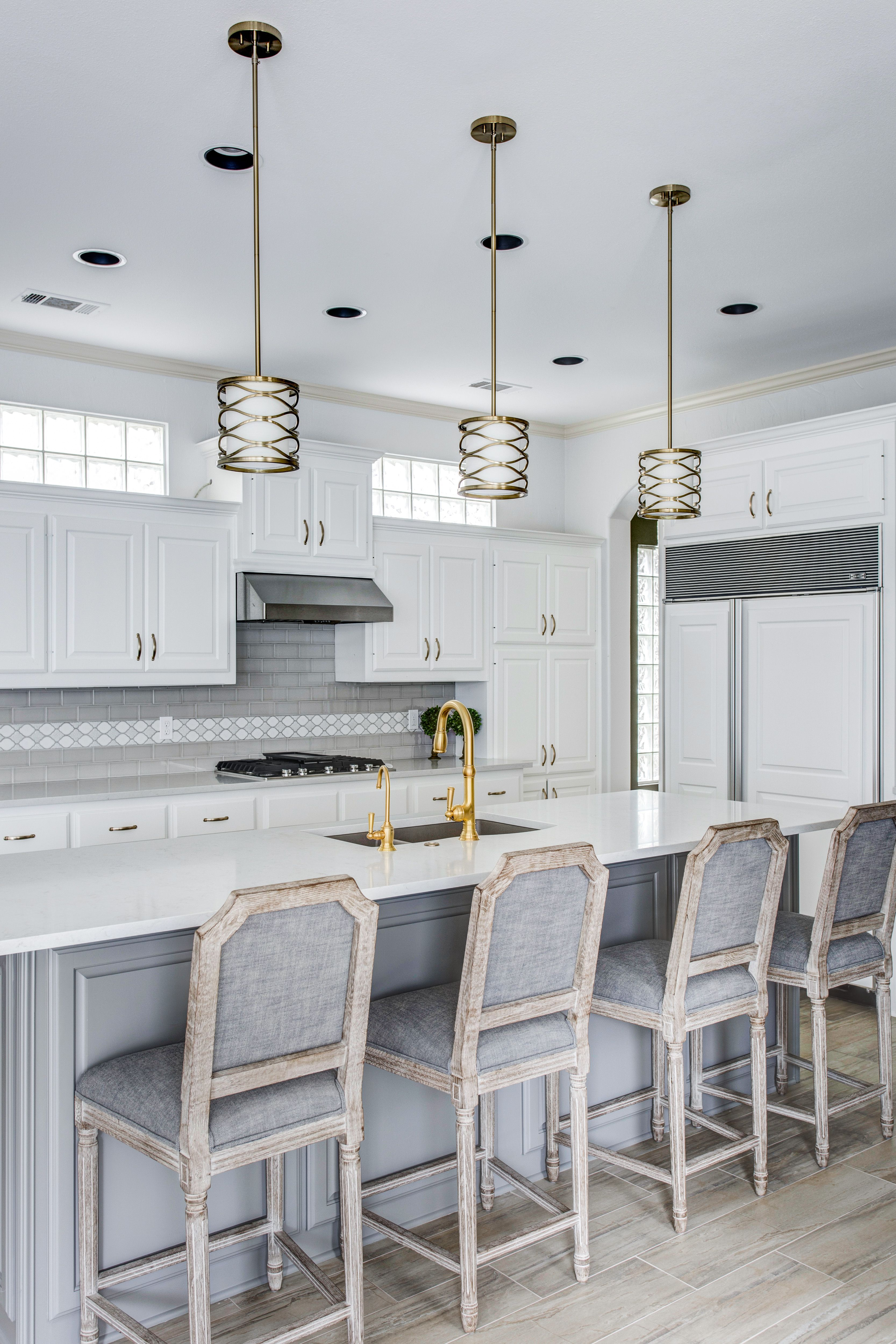 White Cabinets With Grey Subway Tile And A Decorative Glass