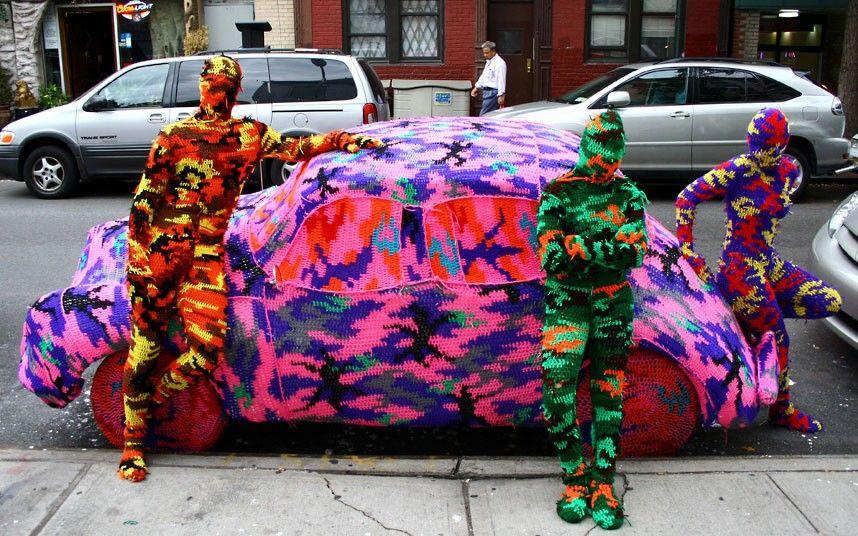 """Ágata Oleksiak es una artista polaca quien vive y trabaja en Nueva York, es conocida alrededor del mundo simplemente como """"Olek"""" y se dedica atejer las calles, parques y galerías de arte con vibrantes colores como fucsia, rojo y amarillo. Su obra es comparada conun caleidoscopio de hilos de lana que se entrelazan hasta formarinstalaciones …"""