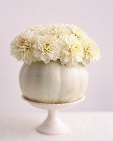 A white pumpkin is transformed into a homemade vase. Select a pumpkin about eight inches in diameter; cut off the top, and scoop out pulp and seeds. Place a small container, such as a highball glass, inside the pumpkin. Trim flowers to fit (we used twelve dahlias, but two dozen carnations would also work), and arrange in the glass.