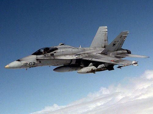 McDonnell Douglas EF-18A Hornet equipado con misiles aire-aire AIM-9 Sidewinder en los extremos de las alas y bombas guiadas por láser GBU-16 Paveway II en el centro de las alas, además de tres depósitos de combustible externos para misiones de largo alcance.