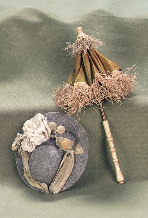 Theriault's Antique Doll Auctions - Antique Parasol and Bonnet for Petite Doll - Comprising a carved bone handle parasol with bone tip,covered with original green silk with ivory silk fringe. Along with a pressed flannel bonnet trimmed with silk ribbons,flowers and berries. Excellent condition,some fading on parasol silk. Circa 1875.