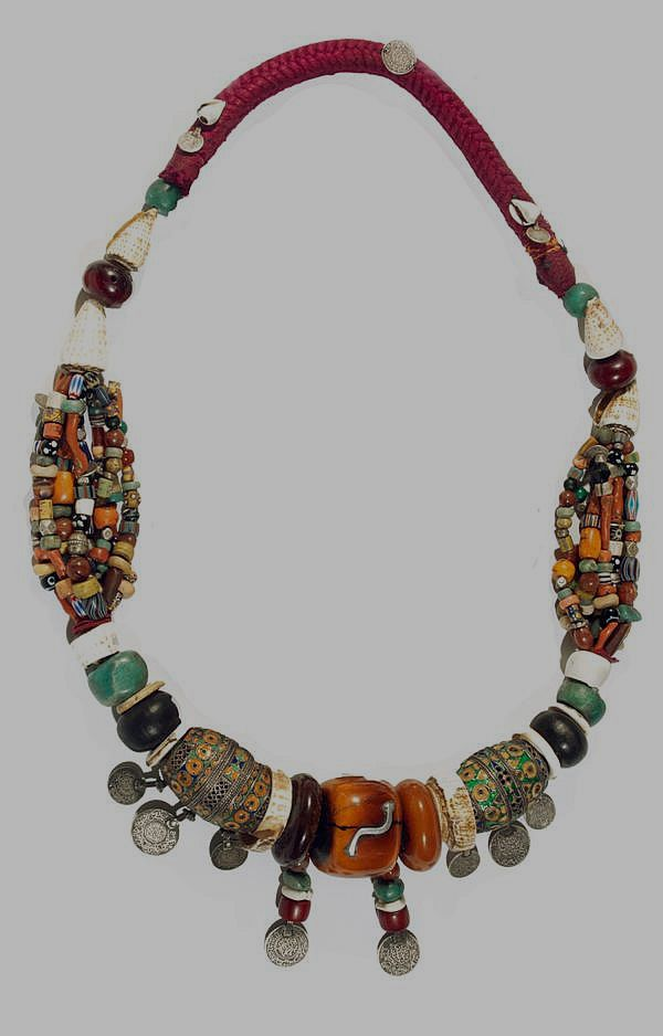 Morocco   Necklace; Two large silver and enamel beads from Tagmout, amber, coral, semi precious stones, glass and silver beads and coins (some dated 1320 and 1331 H)    Souss, Anti Atlas region