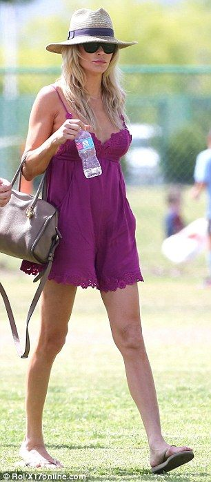 Keeping cool: The reality star had a hat, sunglasses and a bottle of water to help keep he...
