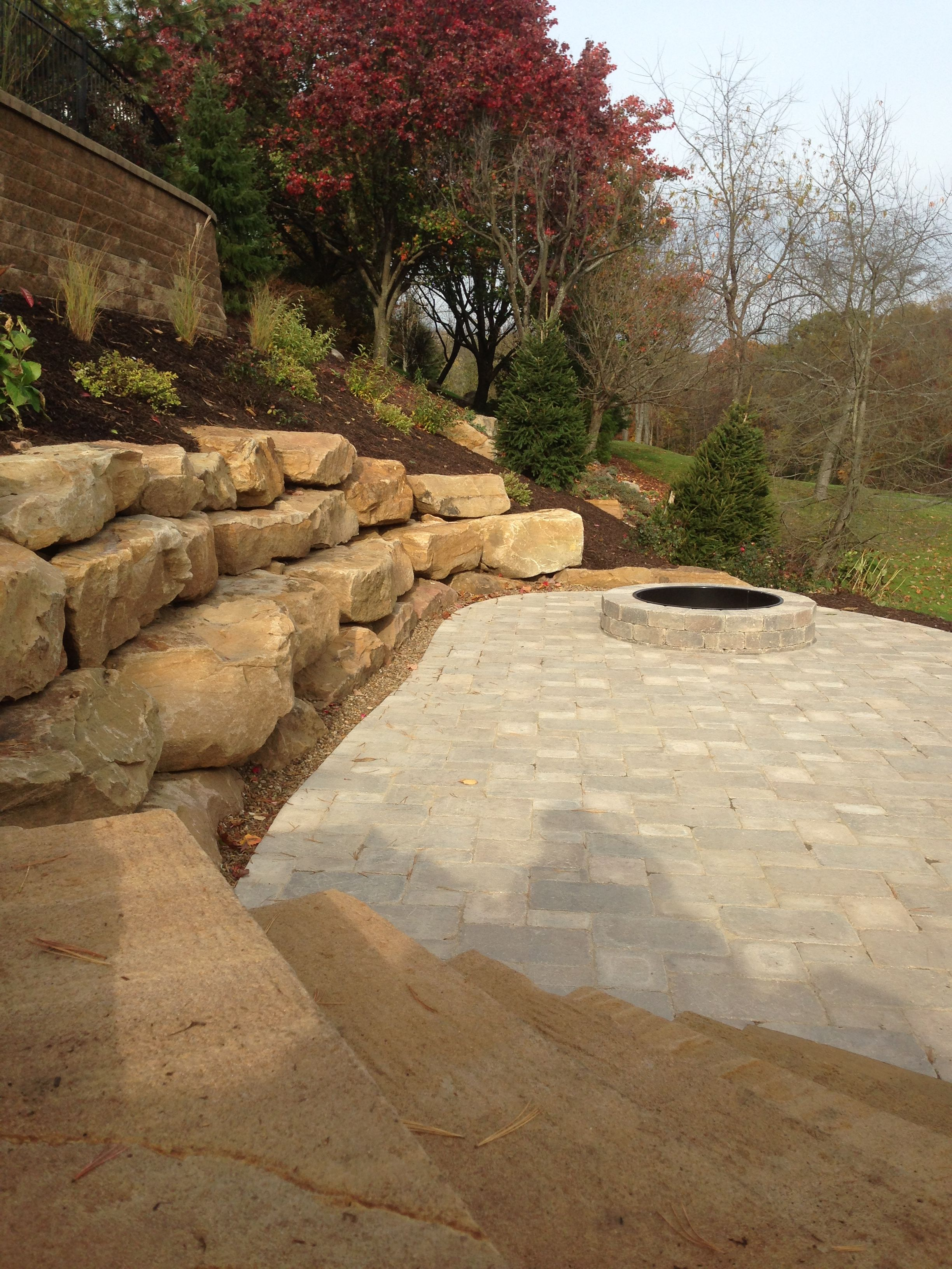 Three Tiered Boulder Retaining Wall Cut Into The Side Of A Hill.