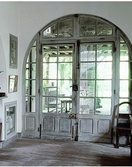 House entry in Provence...Love the gray arched French doors and worn wood.
