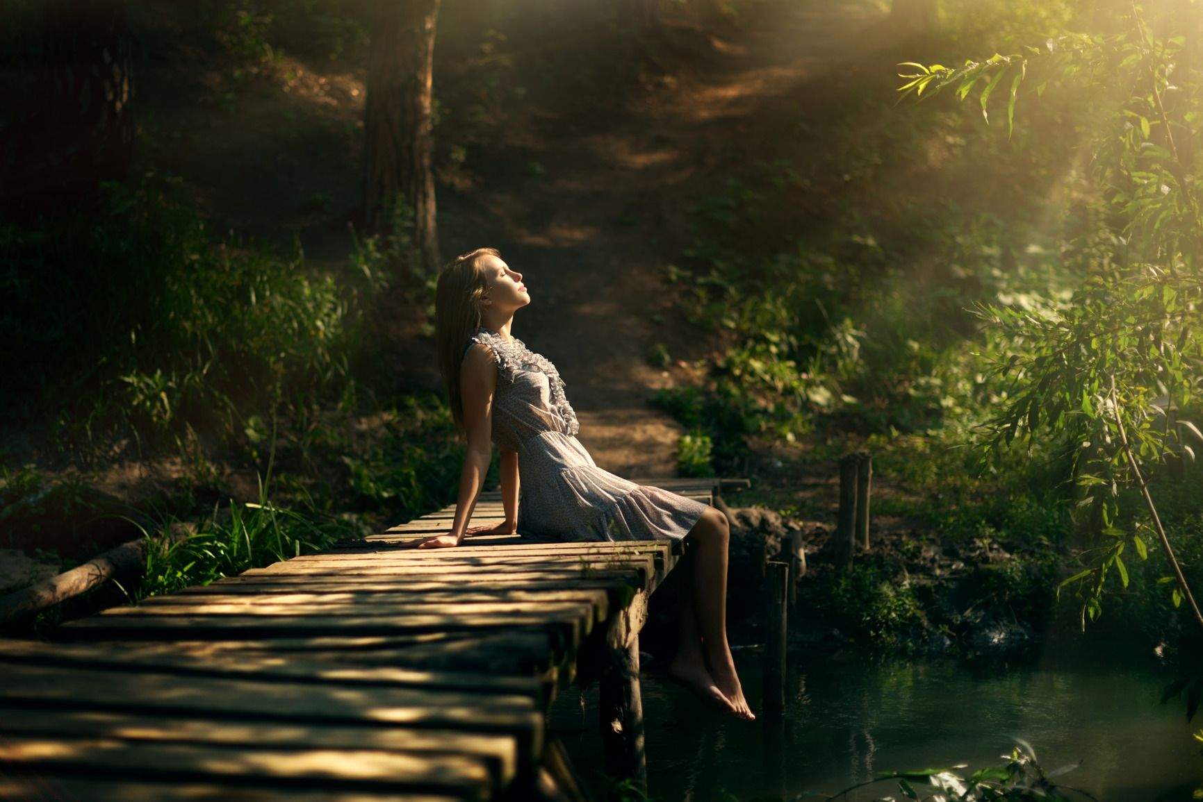 Shot of girl sitting on a wooden bridge over the stream