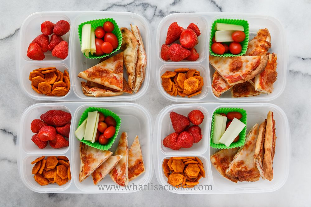 Easy homemade cheese pizzas made on frozen naan bread, with tomatoes, celery, strawberries, and crackers. Packed in  Easy Lunchboxes .