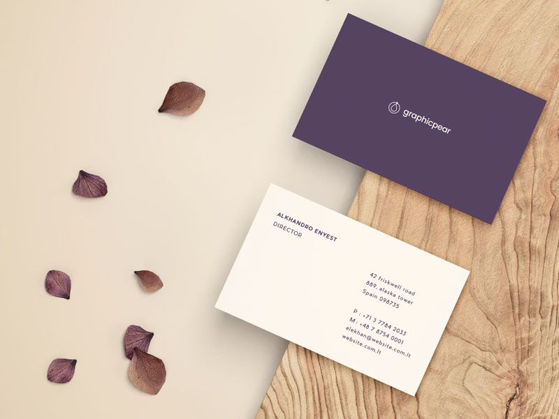 PSD mockup of business card front and back placed on piece of wood ...