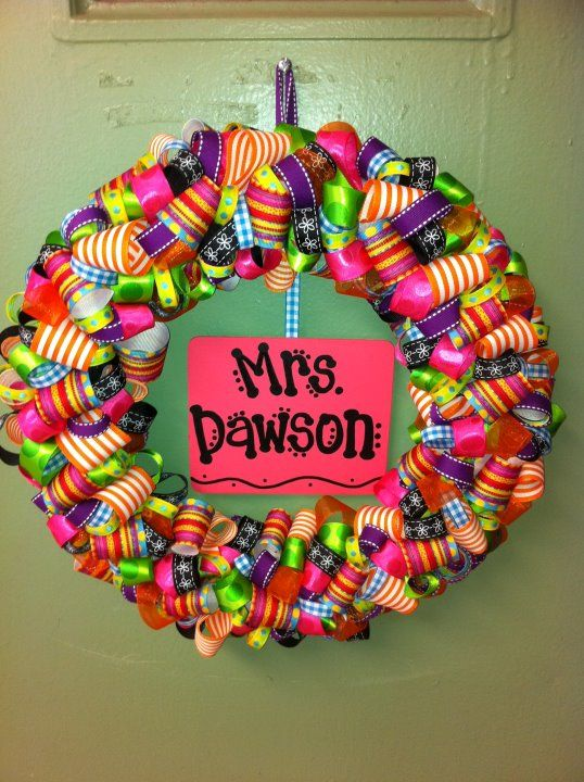 Ribbon wreaths make awesome door hangers or gifts! Super simple. Attach one inch ribbon curls in about 6 different colors to a styrofoam wreath mold using straight pins. I chose to hang a wooden nameplate from the center as well, but this could be left off to accommodate different seasons or styles.