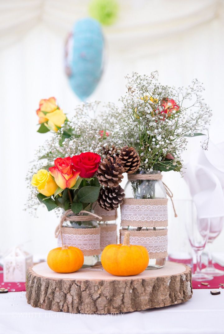 Halloween-Themed Wedding table centerpiece decorations with pine cones, pumpkins on slice of wood