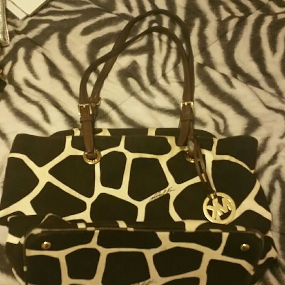Michael kors Giraffe print tote Michael kors tote. Two of four corners have wear. Hardly noticeable.  Handles great shape. Great bag.  Price reflects discount due to wear on corners. Michael Kors Bags
