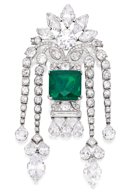 Brooch 1920 Sotheby's   emerald weighing 22.48 carats,  round diamond weighing approximately 3.70 carats, framed by five marquise-shaped diamonds