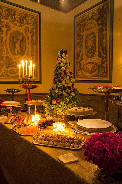 A grand dessert table features delicious cakes, bite sized treats and a tree of pears and grapes.
