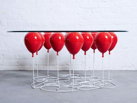 A coffee table that looks like it's being propped up by a bunch of balloons